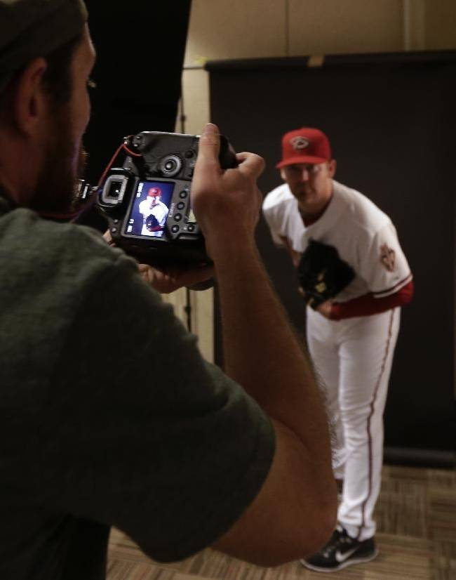 David Wallace, staff photographer for the Arizona Republic newspaper, left, checks the back of his camera as he shoots a portrait of Arizona Diamondbacks pitcher J.J. Putz, right, during the team's photo day before a spring training baseball workout, Wednesday, Feb. 19, 2014, in Scottsdale, Ariz