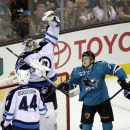 Winnipeg Jets goalie Ondrej Pavelec, of the Czech Republic, leaps to make a save next to San Jose Sharks center Tommy Wingels (57) during the second period of an NHL hockey game Saturday, Oct. 11, 2014, in San Jose, Calif The Associated Press