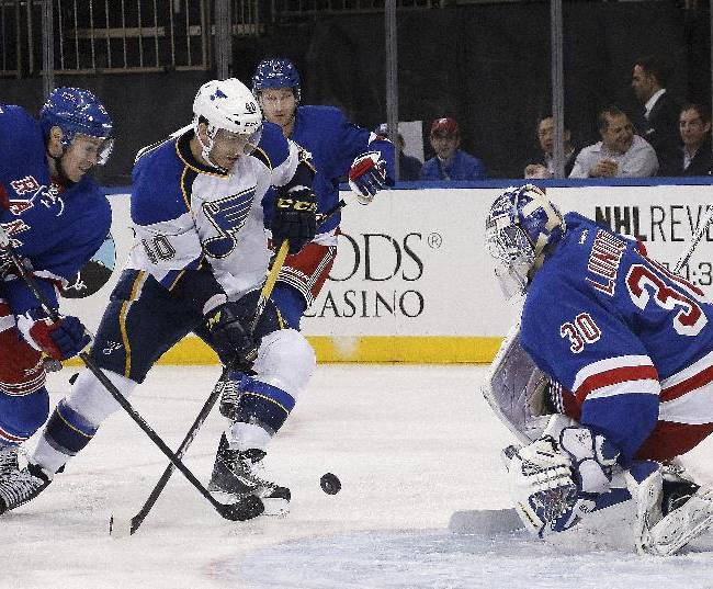 New York Rangers defenseman John Moore (17) defends as St. Louis Blues center Maxim Lapierre (40) lines up a shot in front of Rangers goalie Henrik Lundqvist (30), of Sweden, during the first period of an NHL hockey game at Madison Square Garden in New York, Thursday, Jan. 23, 2014