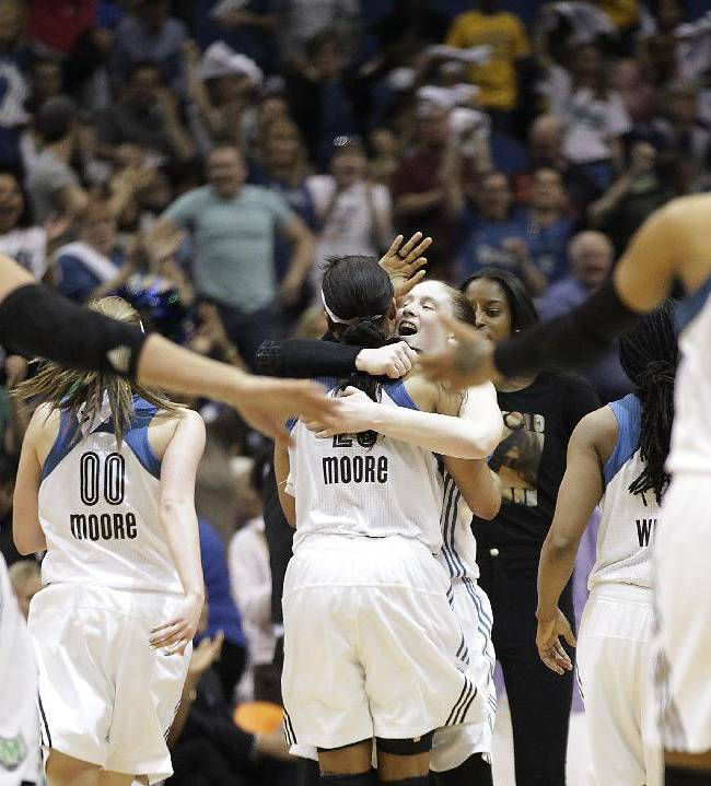 Minnesota Lynx guard Lindsay Whalen (13) hugs teammate guard Maya Moore (23) after the team rallied against the Connecticut Sun in the second half of their WNBA basketball game, Sunday, May 18, 2014, in Minneapolis. The Lynx won 90-87 in overtime