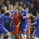 In this photograph taken Wednesday, March 11, 2015, Chelsea players remonstrate with referee Bjorn Kuipers as he holds his red card before showing it to PSG's Zlatan Ibrahimovic during the Champions League round of 16 second leg soccer match between Chels
