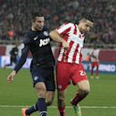 Olympiakos' Kostas Manolas, right, stops the ball ahead of Manchester United's Robin van Persie during their Champions League, round of 16, first leg soccer match at Georgios Karaiskakis stadium, in Piraeus port, near Athens, on Tuesday, Feb. 25, 2014