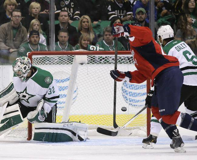 Dallas Stars' Kari Lehtonen, left, of Finland, Washington Capitals' Troy Brouwer, center, and Stars' Trevor Daley (6) watch as a puck flies to the back of the net on a shot by Capitals' Alex Ovechkin n the first period of an NHL hockey game on Saturday, Oct. 5, 2013, in Dallas