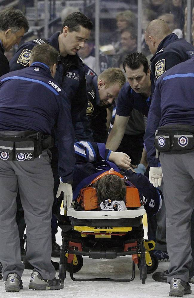 Winnipeg Jets' Jacob Trouba (8) is attended to by paramedics after crashing head first into the boards during the second period of an NHL hockey game, Friday, Oct. 18, 2013 in Winnipeg, Manitoba