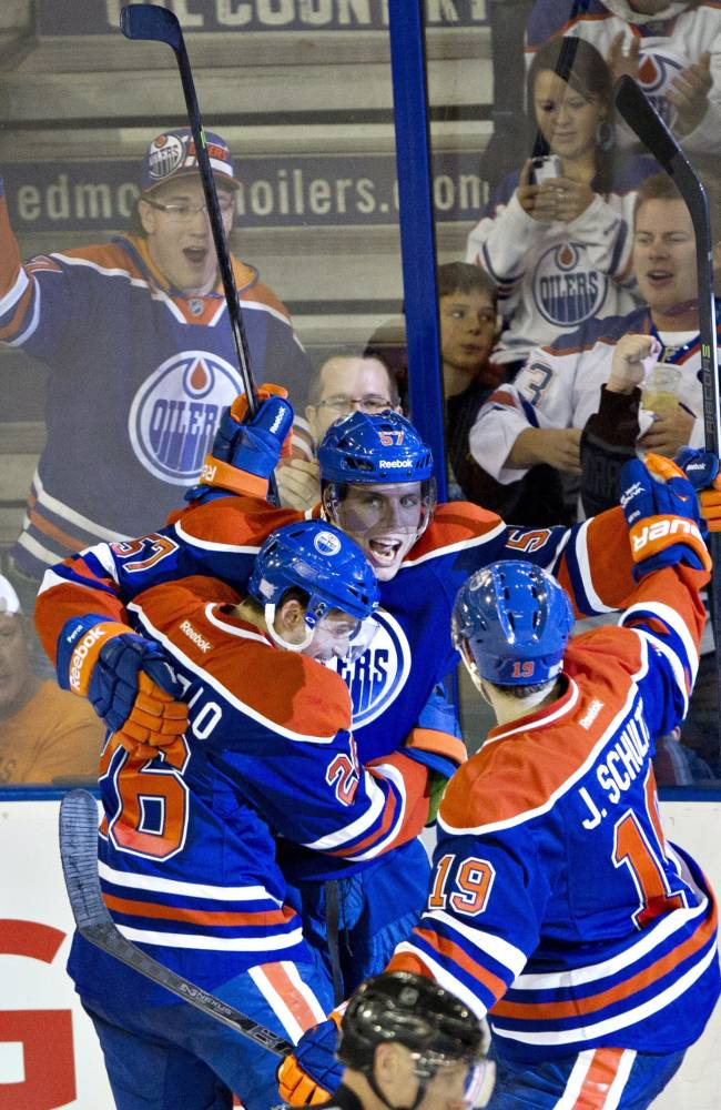 Edmonton Oilers' Mark Arcobello (26), David Perron (57) and Justin Schultz (19) celebrate a goal against the New Jersey Devils during the third period of an NHL hockey game Monday, Oct. 7, 2013, in Edmonton, Alberta. The Oilers won 5-4 in a shootout