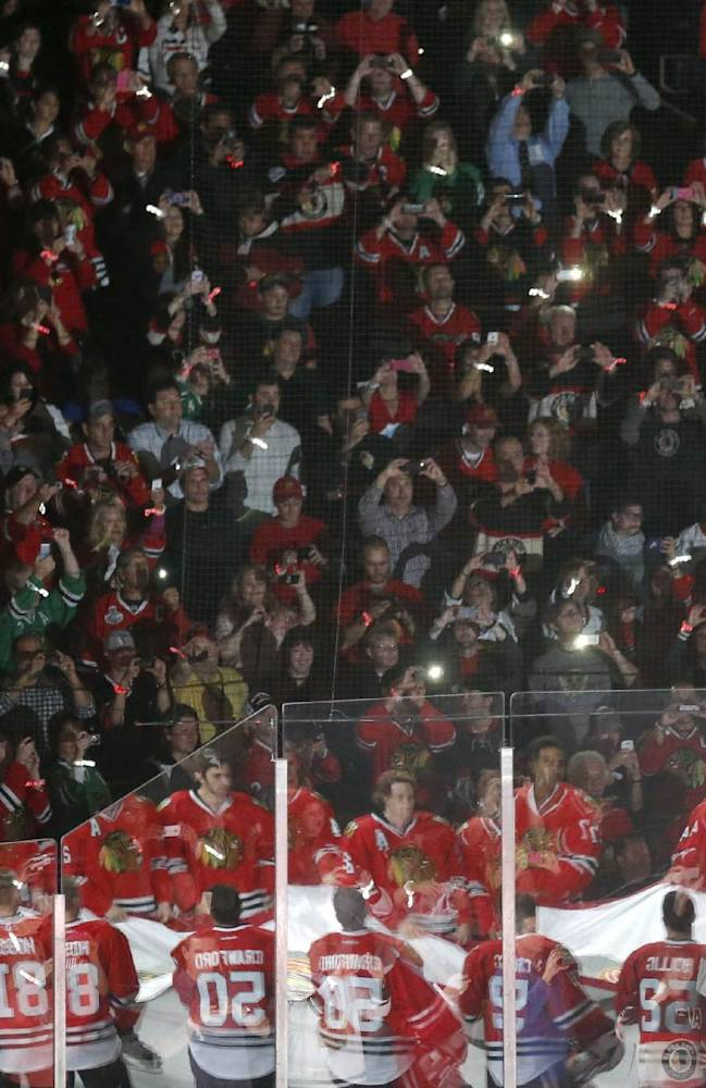 The Chicago Blackhawks are reflected in the glass as they carry out the Stanley Cup Championship banner during ceremonies before an NHL hockey game between the Blackhawks and the Washington Capitals, Tuesday, Oct. 1, 2013, in Chicago
