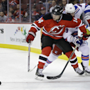 New York Rangers' Ryan Haggerty (39) reaches for the puck around New Jersey Devils' Adam Henrique (14) during the first period of an NHL hockey game Saturday, Oct. 4, 2014, in Newark, N.J The Associated Press