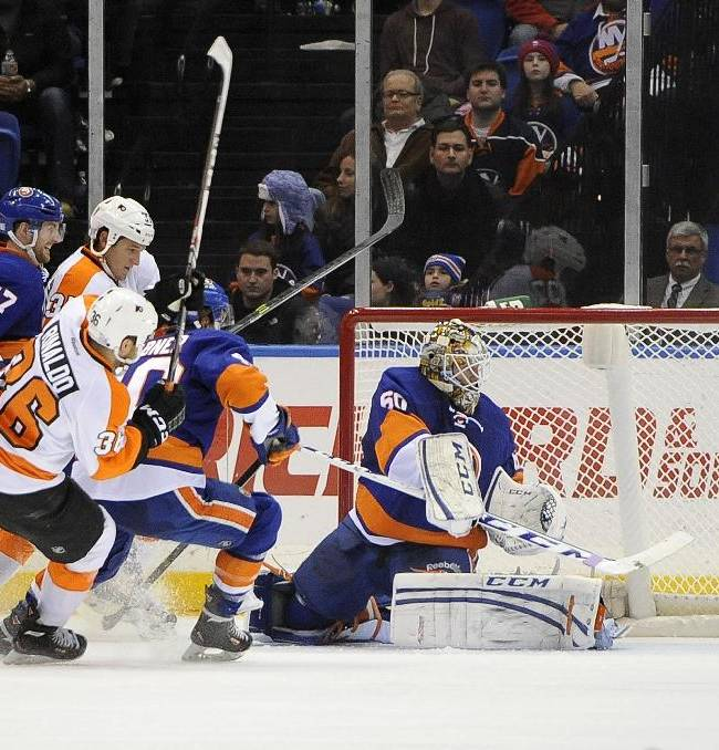 New York Islanders goalie Kevin Poulin (60) drives the puck away from the net pursued by Philadelphia Flyers' Jay Rosehill (37) and Zac Rinaldo (36) in the second period of an NHL hockey game at the Nassau Coliseum on Saturday, Oct. 26, 2013, in Uniondale, N.Y