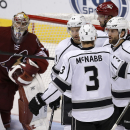 Los Angeles Kings center Jarret Stoll (28), right, celebrates with Brayden McNabb (3) and Justin Williams (14) after scoring against Arizona Coyotes goalie Mike Smith (41) in the second period during an NHL hockey game, Thursday, Dec. 4, 2014, in Glendale