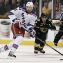 New York Rangers left wing Rick Nash carries the puck up the ice past Boston Bruins' Brad Marchand during the first period of an NHL hockey game in Boston Friday, Nov. 29, 2013 The Associated Press