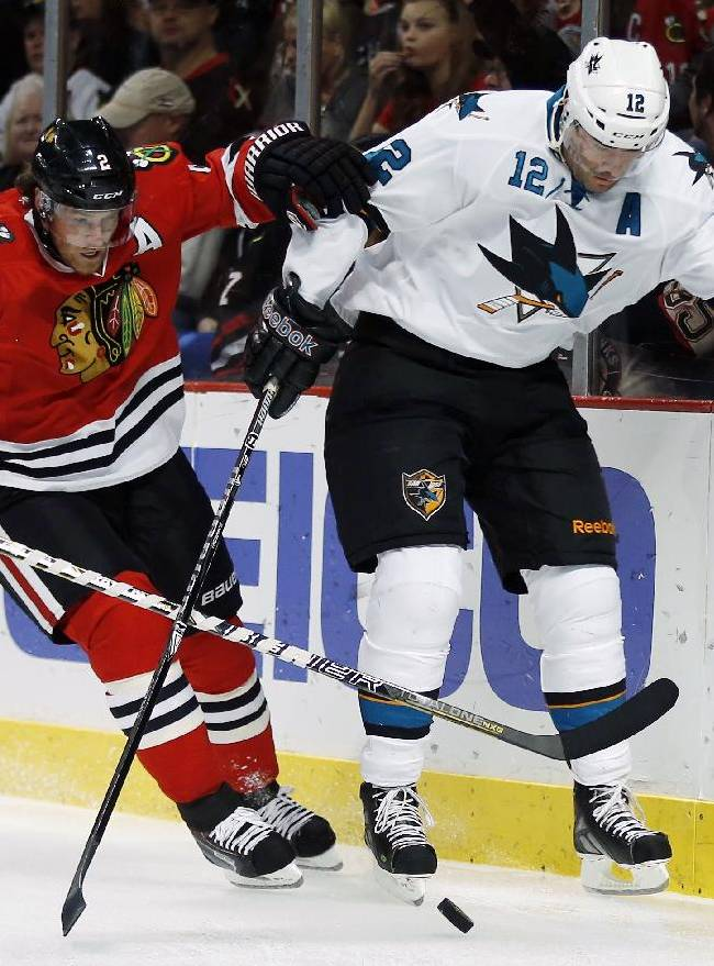 In this Nov. 17, 2013 file photo, Chicago Blackhawks defenseman Duncan Keith (2) and San Jose Sharks left wing Patrick Marleau (12) maneuver with the puck behind the goal during the first period of the NHL hockey in Chicago. Duncan Keith leads all NHL defensemen with 30 assists