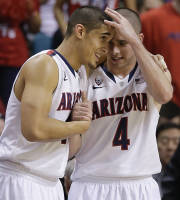 Arizona's Nick Johnson, left, and T.J. McConnell react as they watch play from the bench late in the game against Colorado during the second half of an NCAA college basketball game in the semifinals of the Pac-12 Conference on Friday, March 14, 2014, in Las Vegas. Arizona won 63-43. (AP Photo/Julie Jacobson)