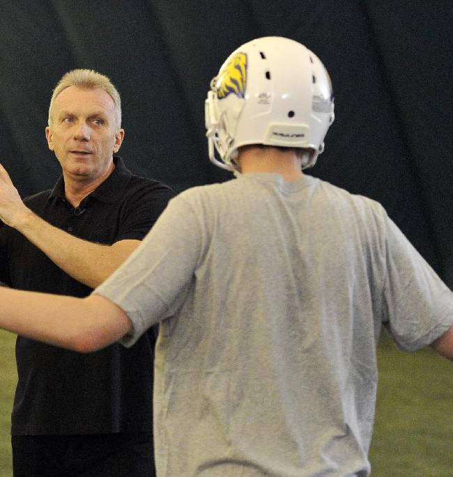 In this image taken on Thursday Oct. 24, 2013 and released by NFL, NFL legend Joe Montana, left, gives instructions during a session with quarterbacks from British universities at Crystal Palace Sports Centre, London. The San Francisco 49ers are due to play the the Jacksonville Jaguars at Wembley stadium in London on Sunday, Oct. 27 in a regular season NFL game