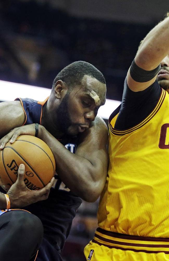 Charlotte Bobcats' Al Jefferson, left, controls a rebound against Cleveland Cavaliers' Anderson Varejao (17), from Brazil, in the fourth quarter of an NBA basketball game on Saturday, April 5, 2014, in Cleveland. Jefferson scored 24 points in the Bobcats' 96-94 overtime win