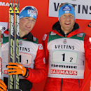Third placed Austria's Sepp Schneider, left, and Bernhard Gruber celebrate on the podium after the team sprint of the Nordic Combined World Cup in Val di Fiemme, northern Italy, Jan. 31, 2015. (AP Photo/Andrea Solero, Ansa)