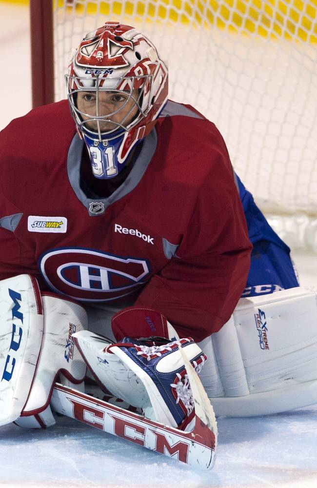 Montreal Canadiens goaltender Carey Price keeps an eye on the action during NHL hockey training camp Thursday, Sept. 12, 2013, in Brossard, Quebec