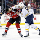 Buffalo Sabres right wing Chris Stewart, right, punches the helmet off New Jersey Devils defenseman Mark Fraser as they fight during the first period of an NHL hockey game, Tuesday, Jan. 6, 2015, in Newark, N.J The Associated Press