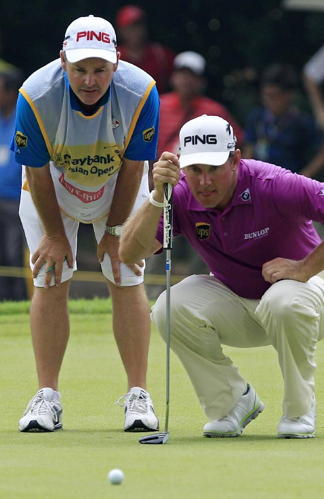 Lee Westwood, right, of England lines up his putt with his caddie on the ninth green during the final round of the Malaysian Open golf tournament at Kuala Lumpur Golf and Country Club in Kuala Lumpur, Malaysia, Sunday, April 20, 2014
