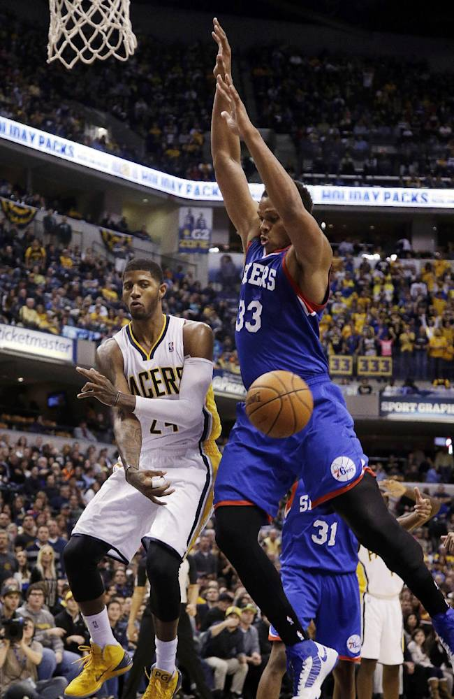 Indiana Pacers forward Paul George, right, passes in front of Philadelphia 76ers center Daniel Orton (33) during the second half of an NBA basketball game in Indianapolis, Saturday, Nov. 23, 2013. The Pacers won 106-98