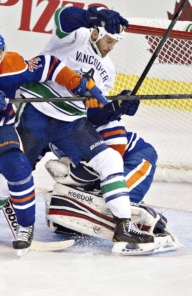 Vancouver Canucks' Zack Kassian, 9, battles in front of the net with Edmonton Oilers' Darnell Nurse, 74, during third period pre-season NHL hockey action in Edmonton, Alta., on Saturday Sept. 21, 2013