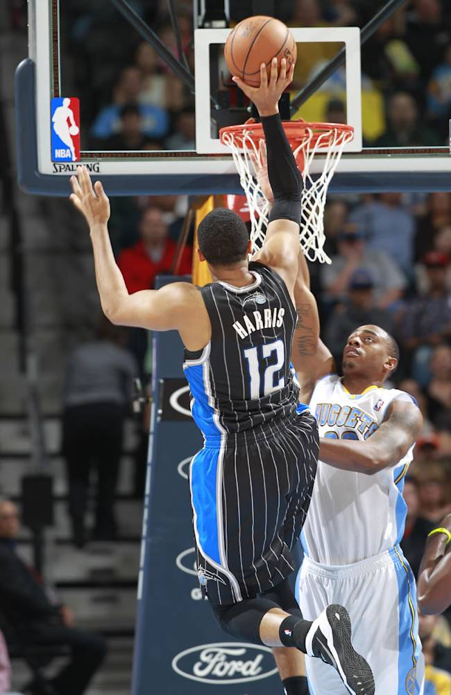 Orlando Magic forward Tobias Harris (12) shoots for a basket over Denver Nuggets guard Randy Foye in the fourth quarter of an NBA basketball game in Denver on Saturday, Jan. 11, 2014