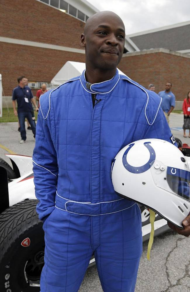Indianapolis Colts receiver Reggie Wayne talks with the media after he arrived in a two-seat IndyCar driven by race driver Ed Carpenter as he and other players arrived for the NFL team's football training camp in Anderson, Ind., Wednesday, July 23, 2014