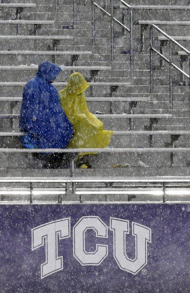 Fans sit in the stands during a thunder delay in the second quarter of an NCAA college football game between Texas and TCU, Saturday, Oct. 26, 2013, in Fort Worth, Texas