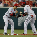 Cincinnati Reds shortstop Eugenio Suarez, left, and second baseman Brandon Phillips (4) celebrate after a baseball game against the Washington Nationals at Nationals Park, Monday, July 6, 2015, in Washington. The Reds won 3-2. (AP Photo/Alex Brandon)