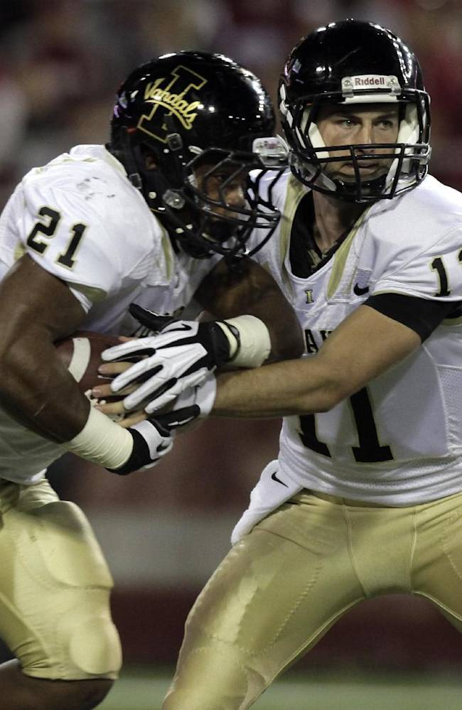 Idaho quarterback Chad Chalich (11) hands off to running back Kristoffer Olugbode (21) during the first quarter of an NCAA college football game against Washington State on Saturday, Sept. 21, 2013, in Pullman, Wash