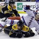 New York Rangers center Brian Boyle (22) goes down to the ice as he chases the puck against Boston Bruins defensemen Adam McQuaid (54) and Torey Krug (47) during the first period in Game 2 of the NHL Eastern Conference semifinal hockey playoff series in Boston, Sunday, May 19, 2013. (AP Photo/Elise Amendola)