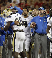 UCLA's Myles Jack (30) is congratulated by linebacker coach Jeff Ulbrich, behind, after recovering the football in the endzone as head coach Jim Mora, right, holds the ball in the second half of an NCAA college football game against Arizona, Saturday, Nov. 9, 2013 in Tucson, Ariz. UCLA won 31 -26. (AP Photo/Wily Low)