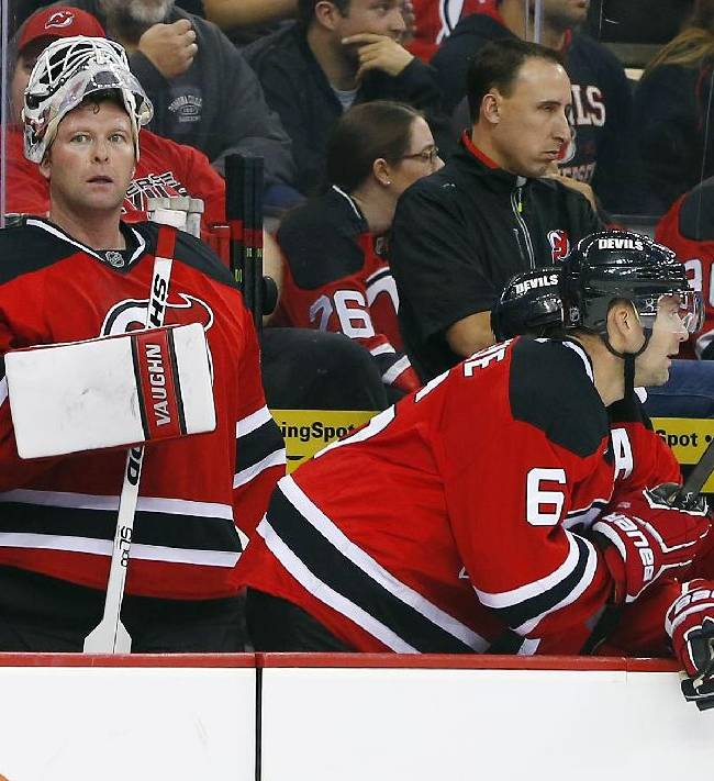 New Jersey Devils' goalie Martin Brodeur, left, watches from the bench after he was pulled from the game in the final minute for an added skater against the Philadelphia Flyers during the third period of an NHL hockey game in Newark, N.J., Saturday, Nov. 2, 2013