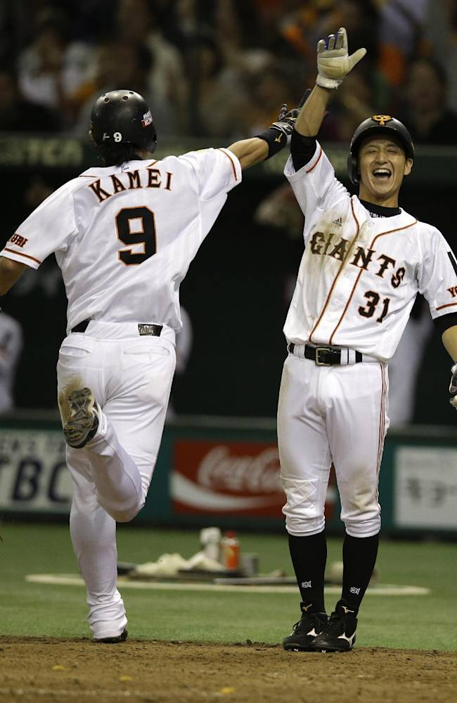 Yomiuri Giants' Tetsuya Matsumoto, right, and Yoshiyuki Kamei (9) celebrate after scoring on a two-run double by Hisayoshi Chono against the Rakuten Eagles in the fifth inning of Game 4 of baseball's Japan Series at Tokyo Dome in Tokyo, Wednesday, Oct. 30, 2013