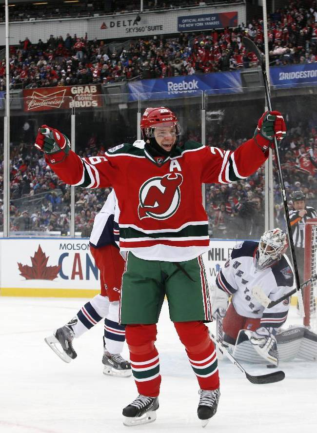 New Jersey Devils left wing Patrik Elias (26), center, celebrates after scoring the second of his two goals in the first period of an NHL outdoor hockey game against the New York Rangers at Yankee Stadium in New York, Sunday, Jan. 26, 2014. It is the first time a hockey game has been played in Yankee Stadium. New Jersey Devils center Travis Zajac (19) looks on,