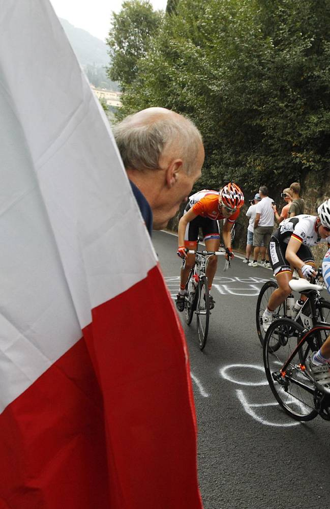 Italy's Angela Maffeis, right,is followed by Germany's Lisa Klein and an unidentified Dutch cyclist as she pedals past an Italian flag during the women's Junior road race event, at the road cycling world championships, in Florence, Italy, Friday, Sept. 27, 2013