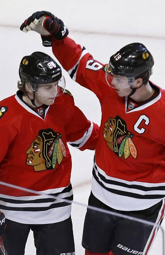 Chicago Blackhawks center Jonathan Toews (19) celebrates his goal with Patrick Kane during the third period of an NHL hockey game against the Columbus Blue Jackets on Thursday, March 6, 2014, in Chicago. The Blackhawks won 6-1