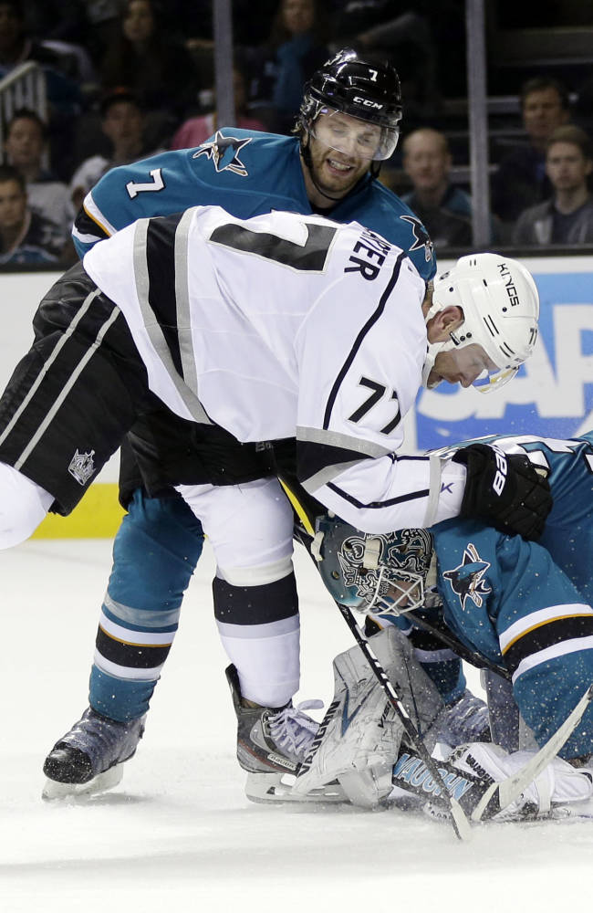 Los Angeles Kings' Jeff Carter (77) collides with San Jose Sharks goalie Antti Niemi, right, of Finland, and defenseman Brad Stuart (7) during the second period of an NHL hockey game Wednesday, Nov. 27, 2013, in San Jose, Calif