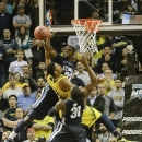 Villanova's JayVaughn Pinkston (22) blocks a shot by Michigan's Zak Irvin (21) during the second half of an NCAA college basketball game Wednesday, Nov. 26, 2014, in New York. Villanova won the game 60-55. (AP Photo/Frank Franklin II)