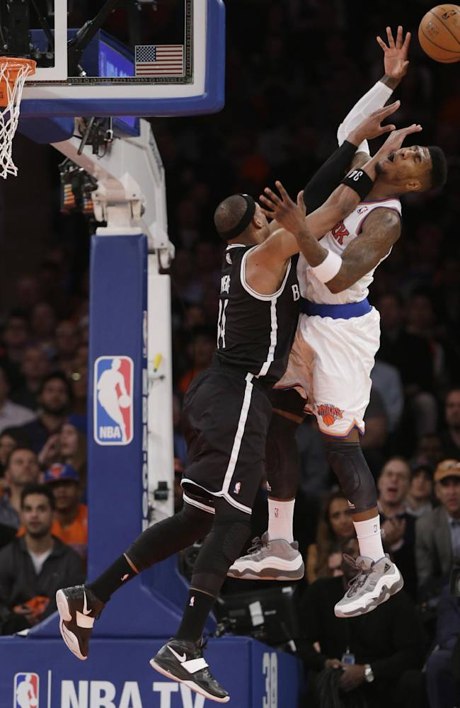Brooklyn Nets' Paul Pierce (34) fouls New York Knicks' Iman Shumpert (21) during the second half of an NBA basketball game Wednesday, April 2, 2014, in New York. The Knicks won the game 110-81