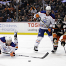 Edmonton Oilers' Taylor Hall, left, misses the puck as Oilers' Ryan Nugent-Hopkins and Anaheim Ducks' Ryan Kesler, right, watch during the third period of an NHL hockey game Wednesday, Dec. 10, 2014, in Anaheim, Calif. The Ducks won 2-1 The Associated Pre