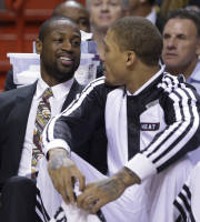 Miami Heat guard Dwyane Wade, right, chats with forward Michael Beasley as they sit on the bench during the first half of an NBA basketball game against the Atlanta Hawks, Tuesday, Nov. 19, 2013 in Miami. Wade sat out Miami's game against the Atlanta Hawks on Tuesday night, the second time this season that the Heat guard has been held out for rest purposes. (AP Photo/Wilfredo Lee)