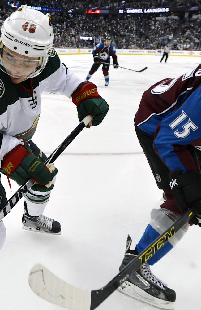 Minnesota Wild defenseman Jared Spurgeon (46) and Colorado Avalanche right wing P.A. Parenteau (15) eye the puck in the second period of Game 2 of an NHL hockey first-round playoff series on Saturday, April 19, 2014, in Denver