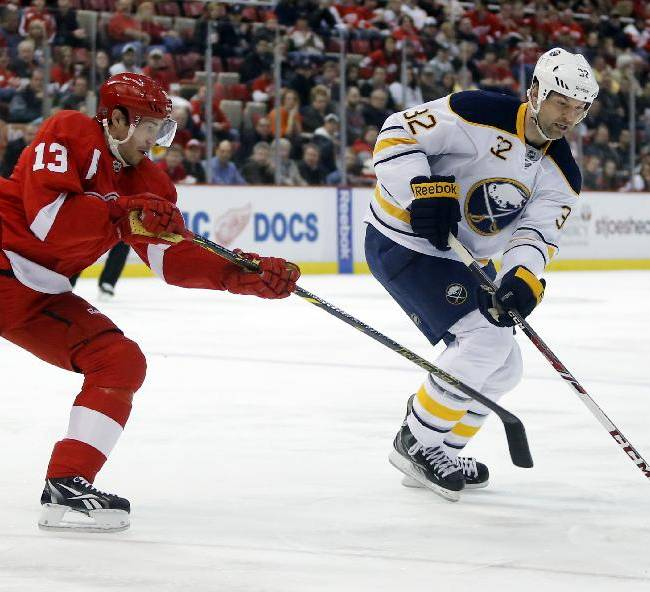 Detroit Red Wings' Pavel Datsyuk (13), of Russia, tries to get to the puck controlled by Buffalo Sabres' John Scott (32) during the first period of an NHL hockey game Friday, April 4, 2014, in Detroit. The Red Wings defeated the Sabres 3-2