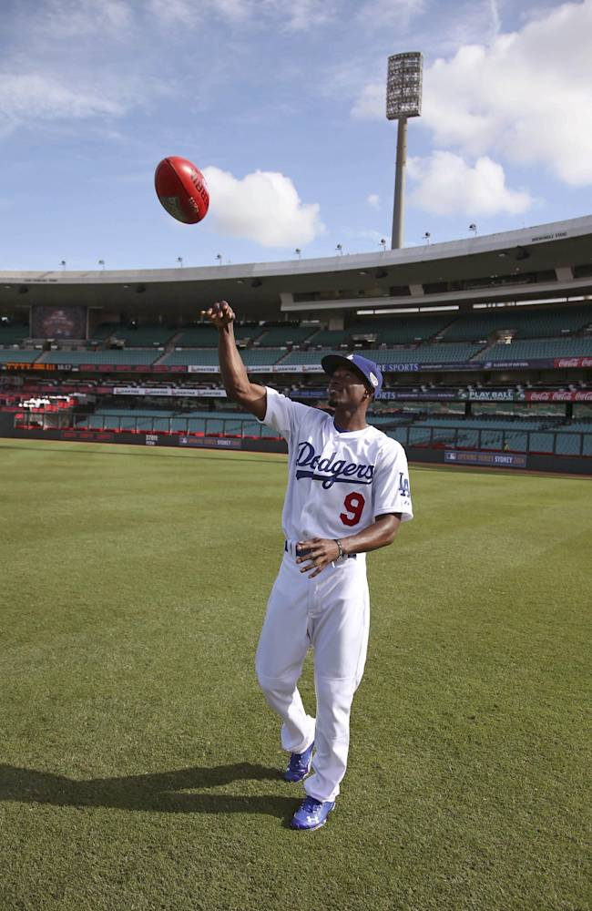 The Los Angeles Dodgers' Dee Gordon throws an Australian rules football during a training at the Sydney Cricket Ground in Sydney, Wednesday, March 19, 2014. The MLB season-opening two-game series between the Los Angeles Dodgers and Arizona Diamondbacks in Sydney will be played this weekend