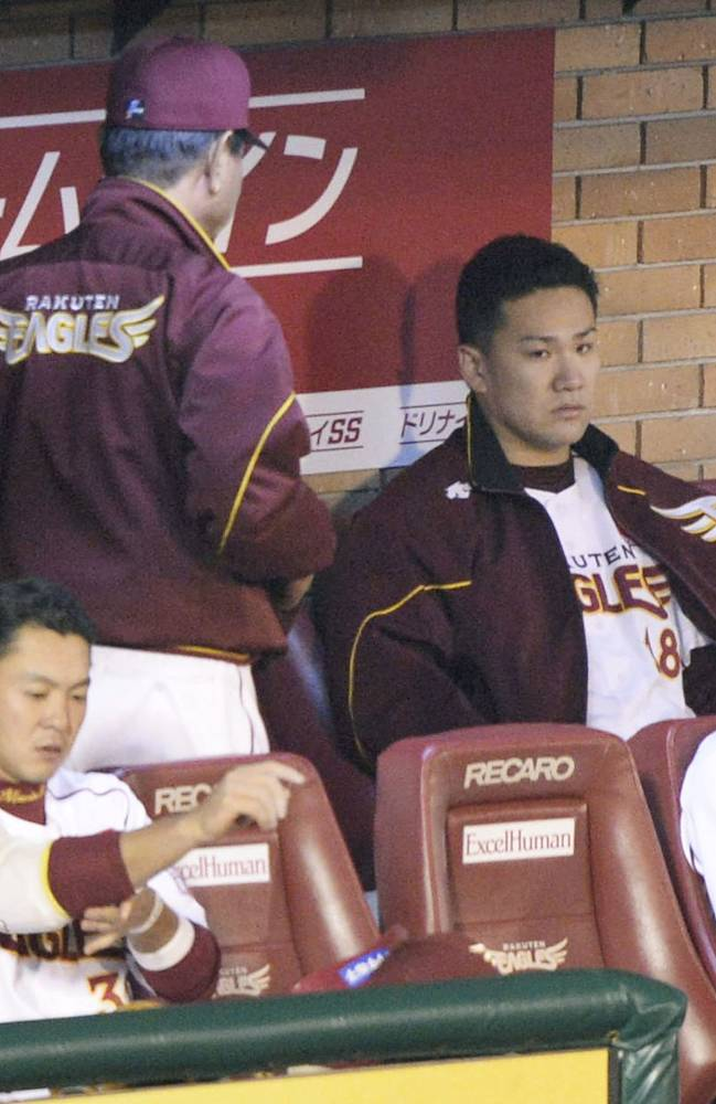 Rakuten Eagles starter Masahiro Tanaka, right, sits in the dugout after completing Game 6 of baseball's Japan Series against the Yomiuri Giants at the Kleenex Stadium Miyagi in Sendai, northeastern Japan, Saturday, Nov. 2, 2013. The Giants won the game 4-2 and handed Tanaka his first loss since Aug. 19, 2012. Standing at left is manager Senichi Hoshino