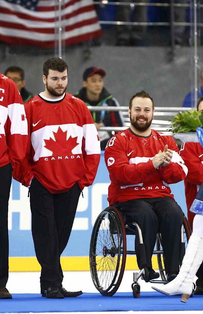 Canada players wait to receive their bronze medals during the medal ceremony after the gold ice sledge hockey match between United States and Russia at the 2014 Winter Paralympics in Sochi, Russia, Saturday, March 15, 2014. United States won the gold medal