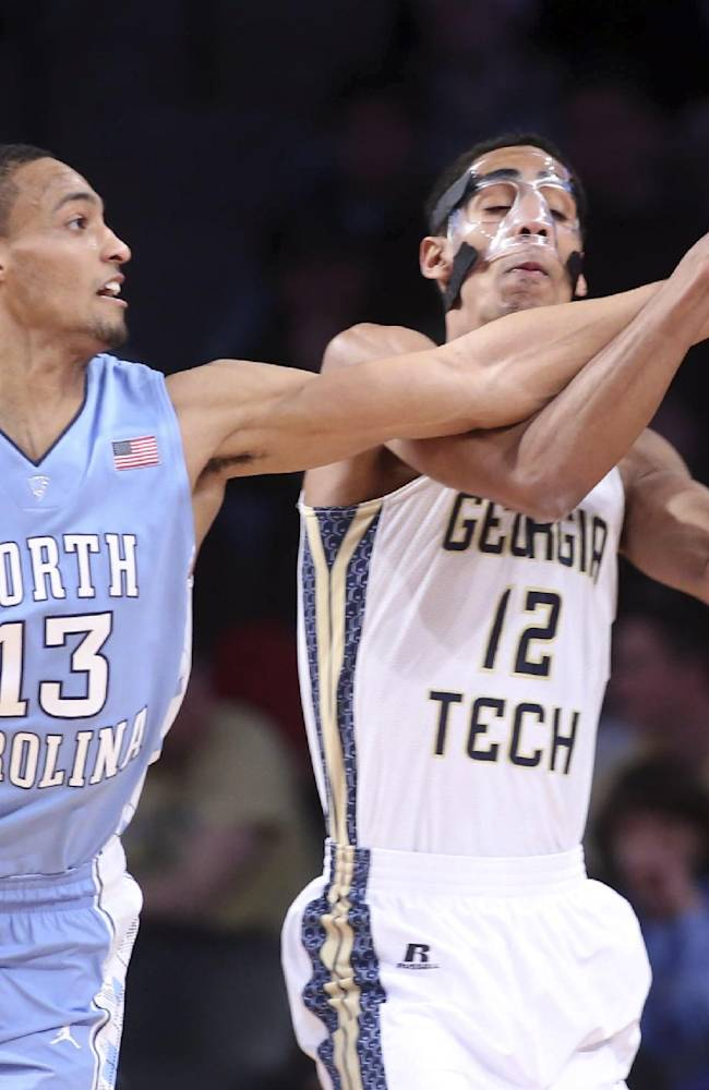 North Carolina forward J.P. Tokoto (13) fights for a loose ball with Georgia Tech guard Quinton Stephens (12) in the first half of an NCAA college basketball game, Wednesday, Jan. 29, 2014, in Atlanta