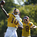 Washington Redskins quarterbacks Robert Griffin III, left, and Kirk Cousins throw during practice at the team's NFL football training facility, Monday, July 28, 2014 in Richmond, Va The Associated Press
