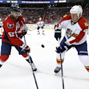 The loose puck bounces between Washington Capitals defenseman Mike Green (52) and Florida Panthers defenseman Dylan Olsen (4) during the first period of an NHL hockey game, Saturday, Oct. 18, 2014, in Washington The Associated Press
