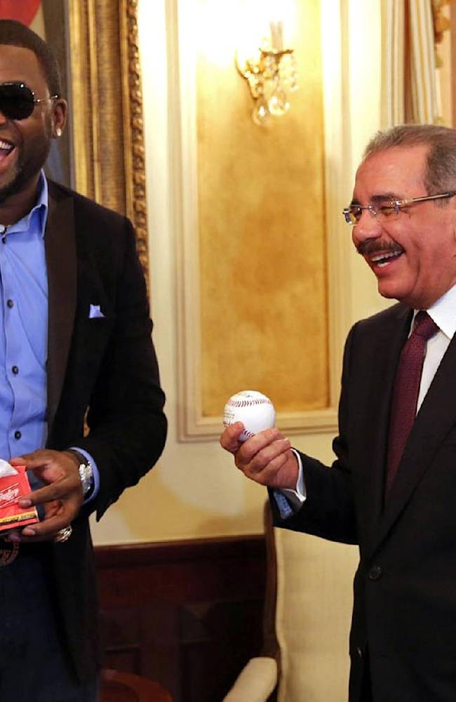 Boston Red Sox designated hitter David Ortiz, left, and Dominican Republic President Danilo Medina laugh after Ortiz presented his country's president with a ball and a bat during a meeting at the National Palace in Santo Domingo, Dominican Republic, Thursday, Nov. 28, 2013. Ortiz and fellow players of the Dominican Republic baseball team are in Santo Domingo to receive their champions rings for winning the 2013 World Baseball Classic in March